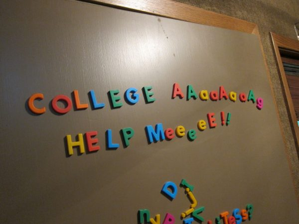 "Magnetic letters on the front door spell out ""College Aaaaahhhh help meeeeee....."""
