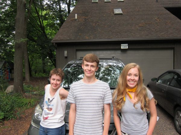 Triplets, posing in front of a packed van, ready to leave for college.