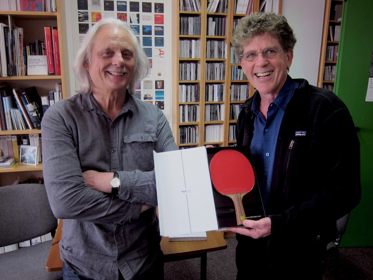 Manfred Eicher receives the gift of a Killerspin 800 ping-pong paddle from Steve Tibbetts